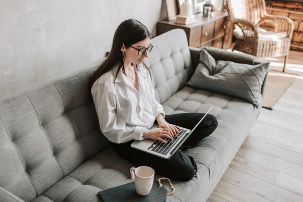 Woman wearing white shirt working on a laptop while sitting on a grey couch