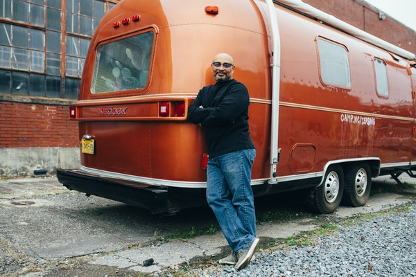 Older black gentleman standing next to an orange vintage RV