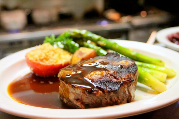 Steak covered in BBQ sauce on white dinner plate with asparagus