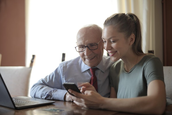 Daughter wearing green shirt showing her elderly father something on her phone
