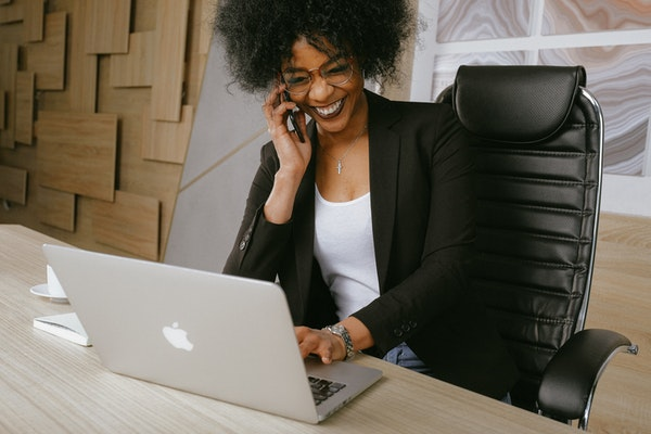 Black businesswoman working on an Apple laptop while talking on the phone