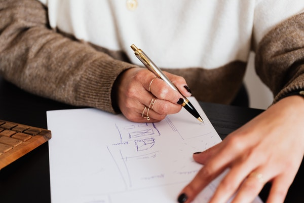 Woman scribbling house plans on a piece of white paper