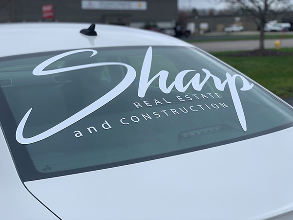 Back windshield of Sharp Real Estate and Construction car