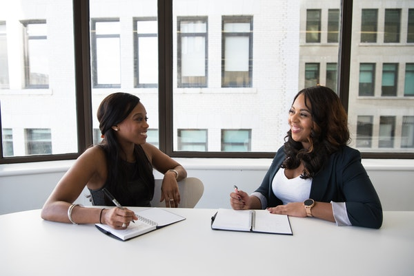 Two black women networking at an office