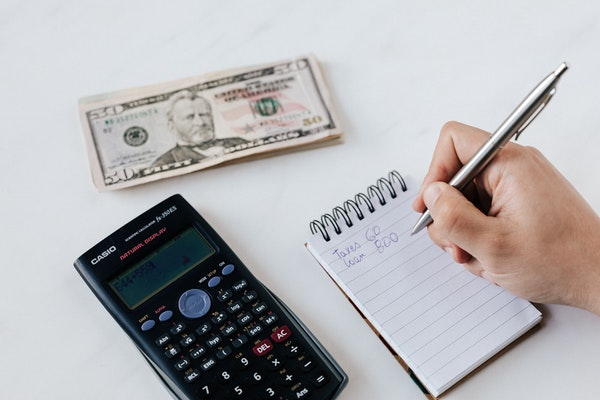 Person writing on a notepad next to a calculator and stack of money