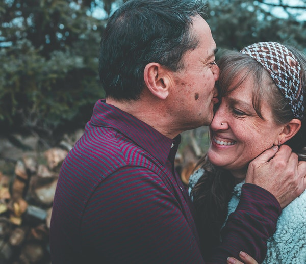 Man in maroon shirt kissing woman on forehead