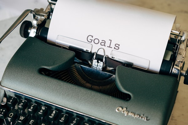"""""""Goals"""" typed out on a paper coming out of a typewriter"""
