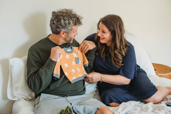 Husband and wife sitting on bed holding up baby clothes