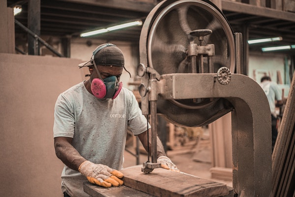 Black male manufacturing employee working at a machine
