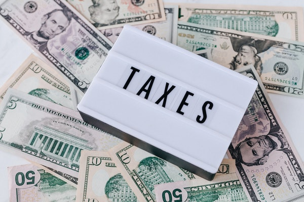 Taxes sign on top of a pile of cash