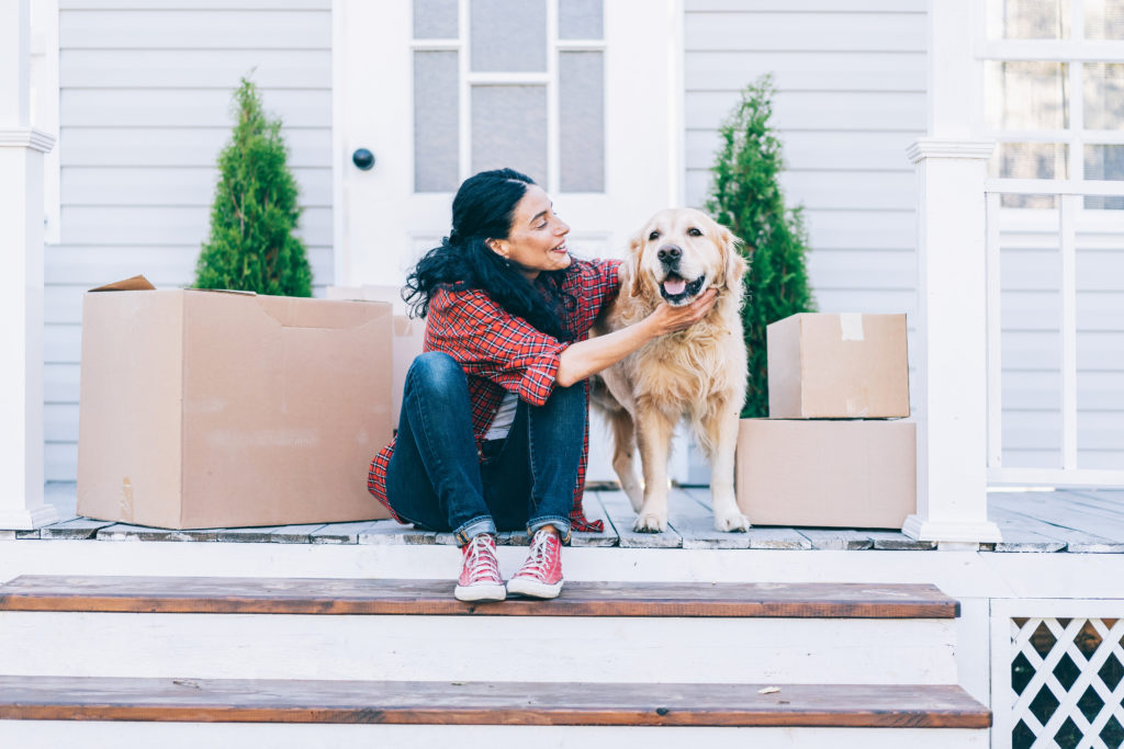 Woman sitting on porch steps petting a golden retriever