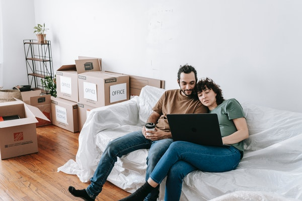 Couple in the process of moving planning on a futon