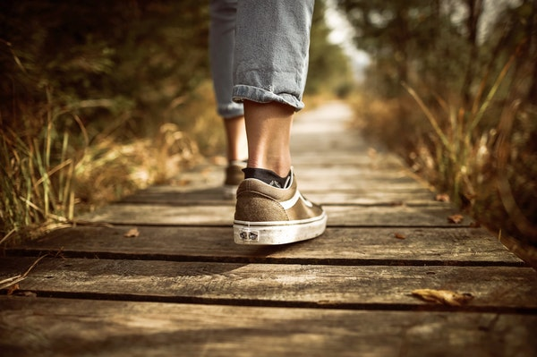 Up close of person's shoes walking over wooden bridge in woods