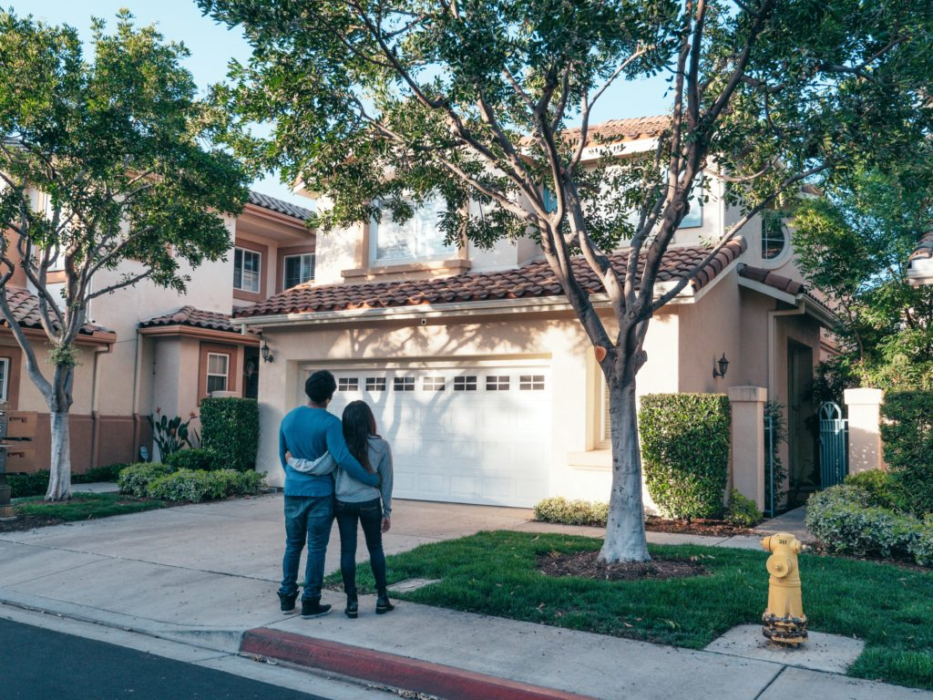 Couple standing on a sidewalk looking up at a house.