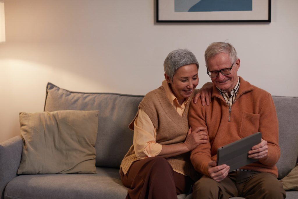 Older couple sitting on a sofa and looking at a computer.