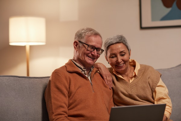 Mature husband and wife looking at computer on sofa