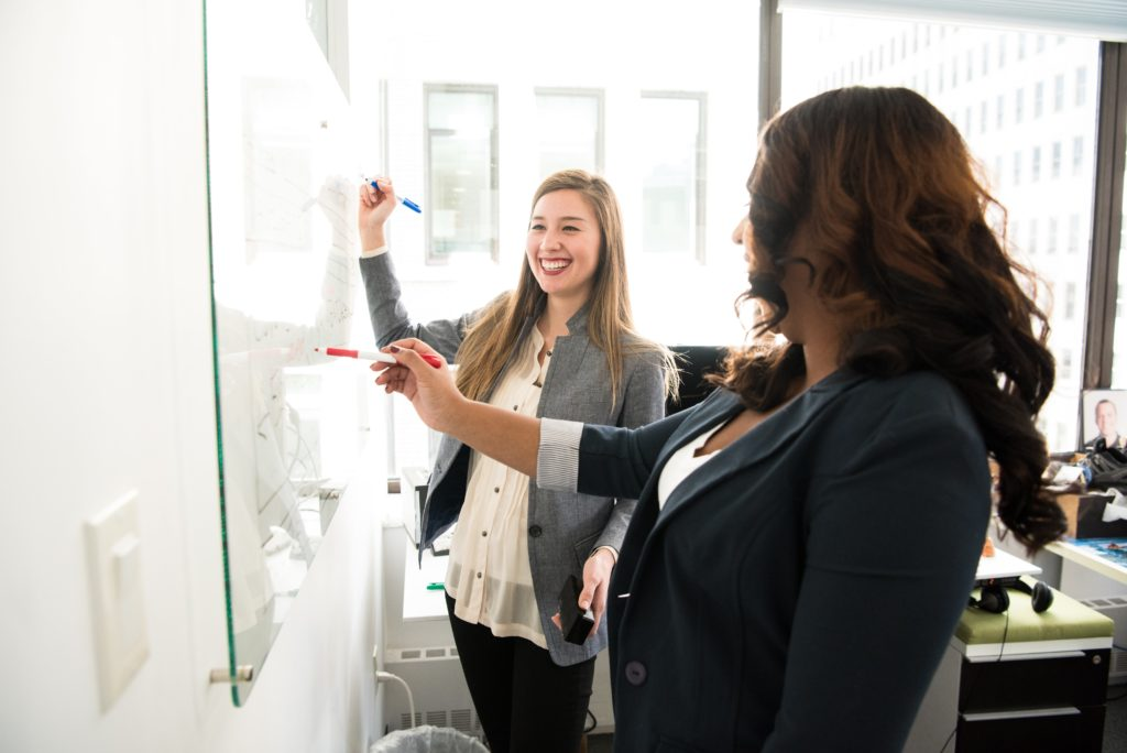 Two female professionals brainstorming on a whiteboard in an office.