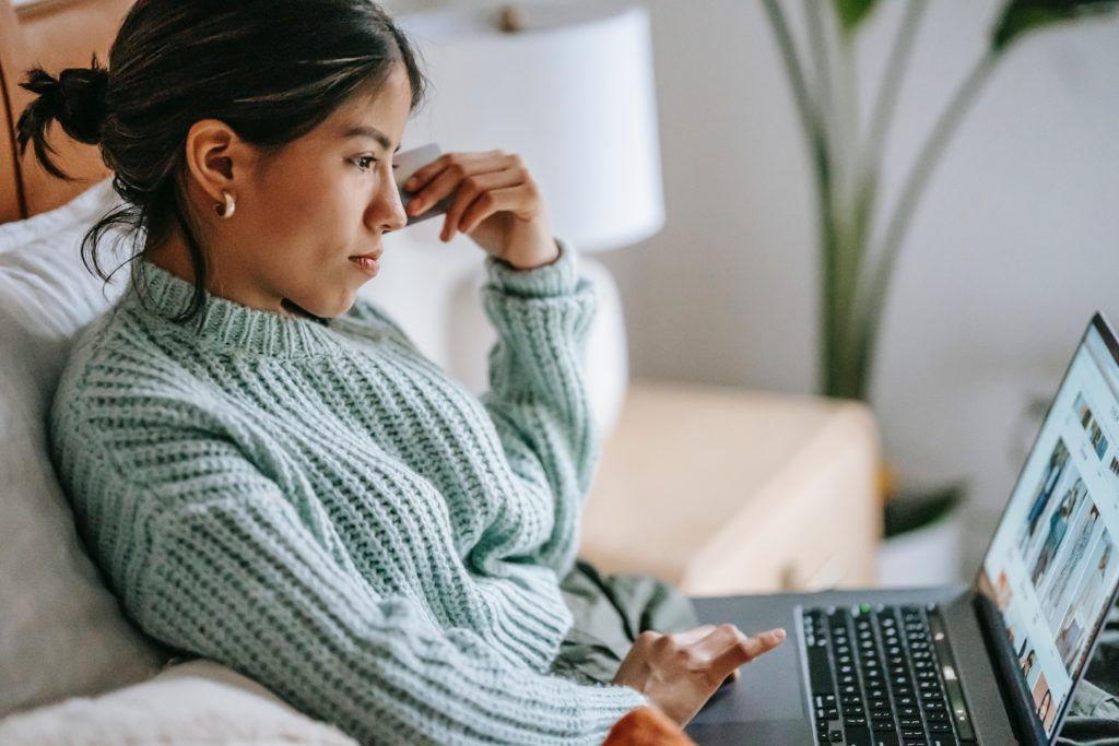 Woman sitting on sofa, shopping online while she holds a credit card.