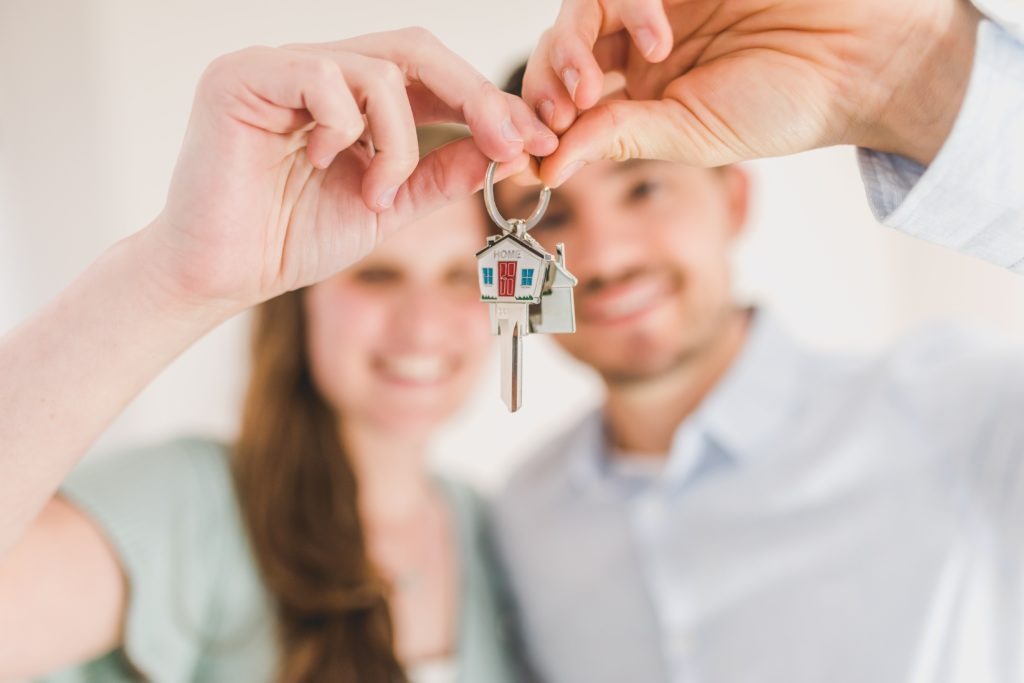 Male and female couple holding a new set of house keys.