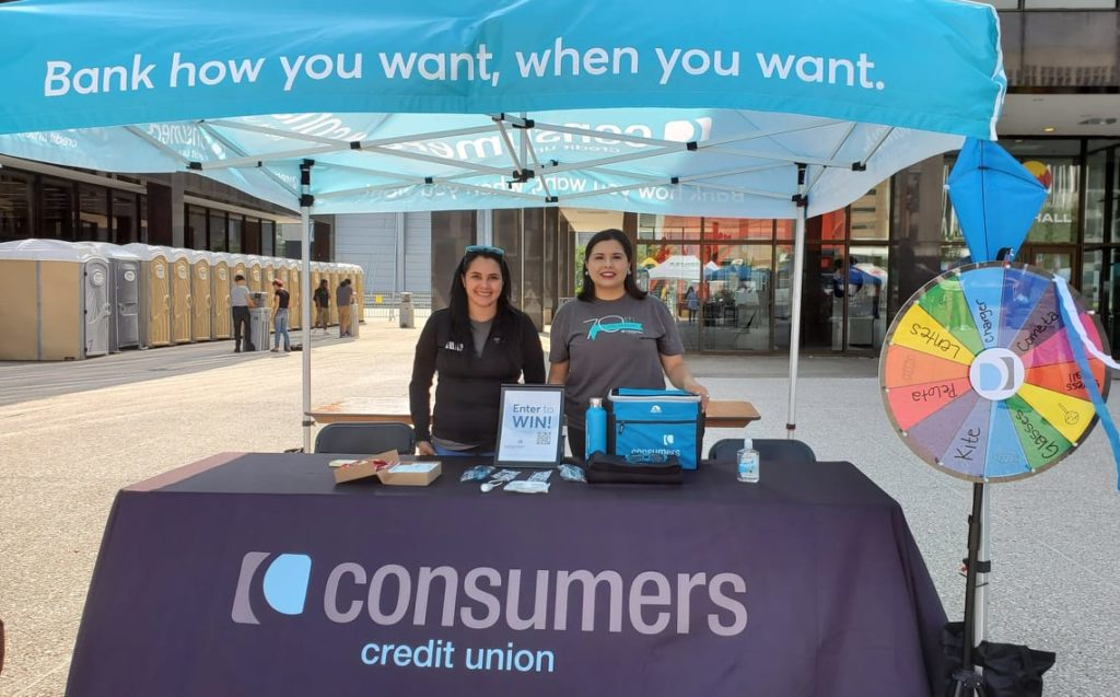 Two Consumers team members hosting a booth at the Grand Rapids Hispanic Festival on a sunny day.