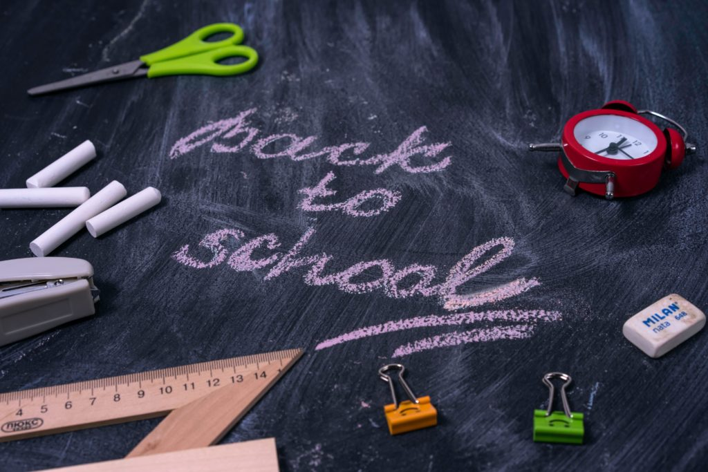 """""""Back to School"""" written on a chalkboard littered with rulers, paperclips and other school supplies."""