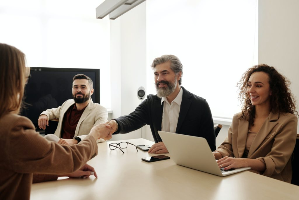 Three professionals sitting across a table from a woman during a job interview.