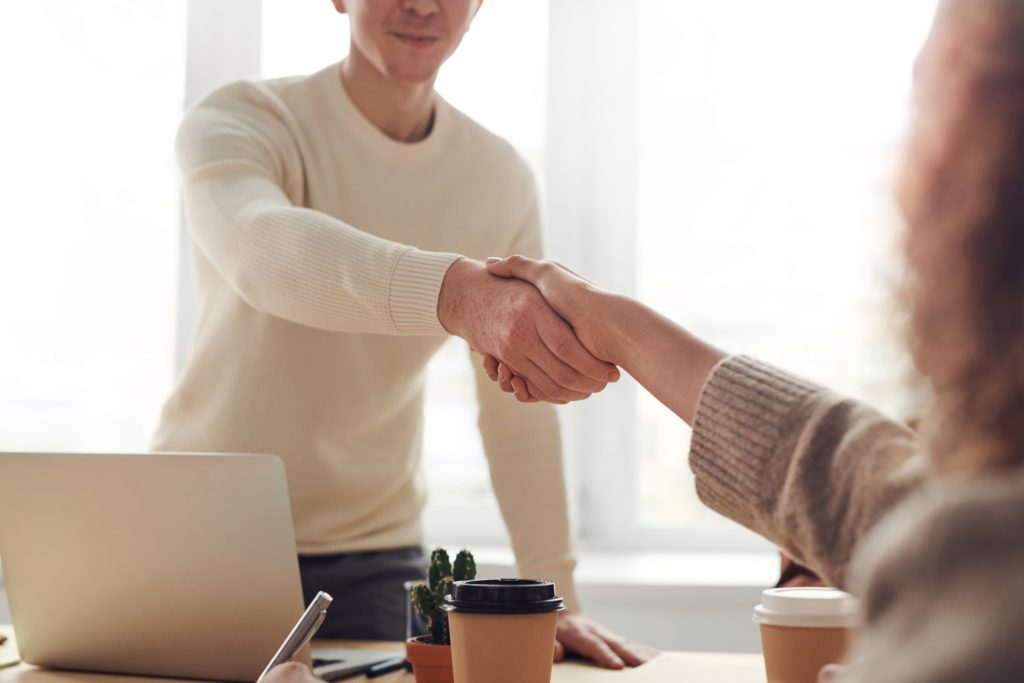 Two people shake hands over a table during a job interview.