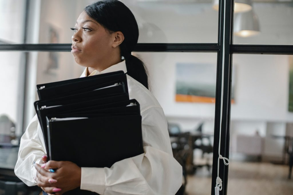 Woman holding an armful of black binders in a business office.
