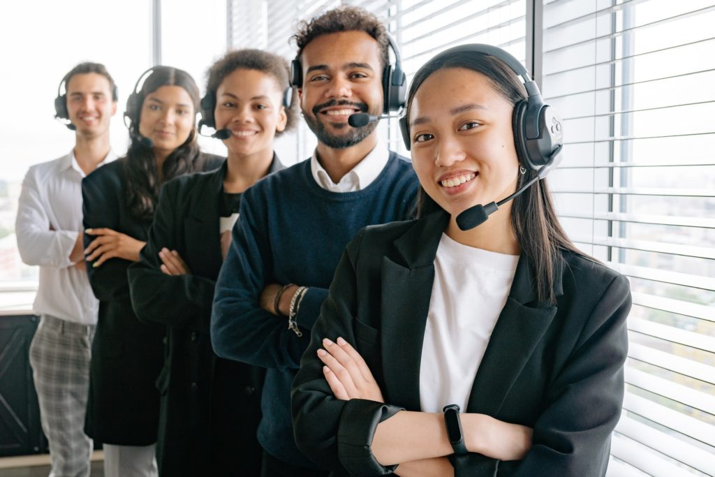 Five smiling professionals with headsets stand in a staggered line ready to help clients.