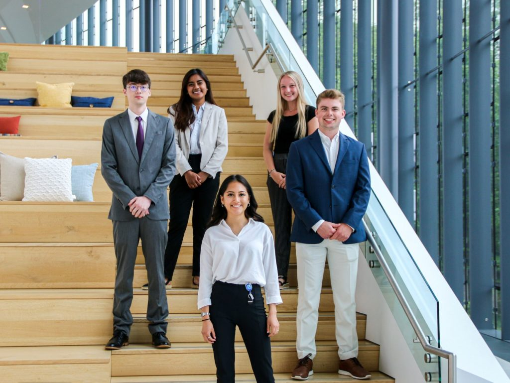Consumers 2021 Summer Interns smiling for the camera on the atrium staircase.