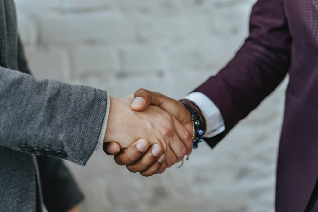 Two people is business suits shake hands.