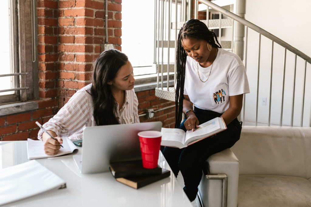 Two women studying in a college apartment.