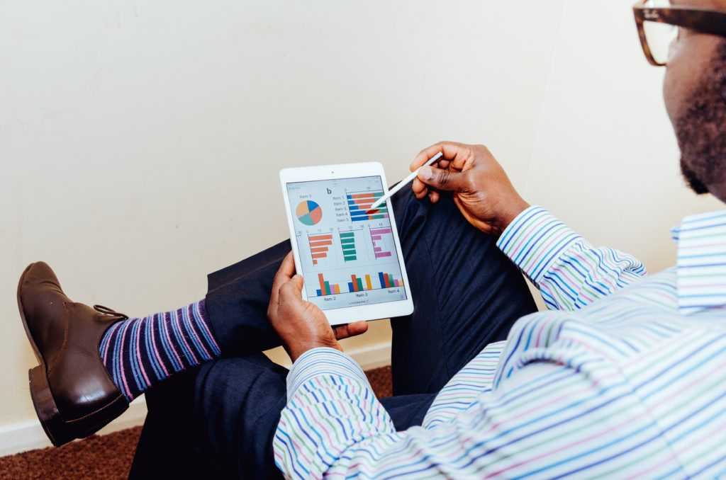 A man sitting on a chair with crossed legs reviewing his finances on an iPad.