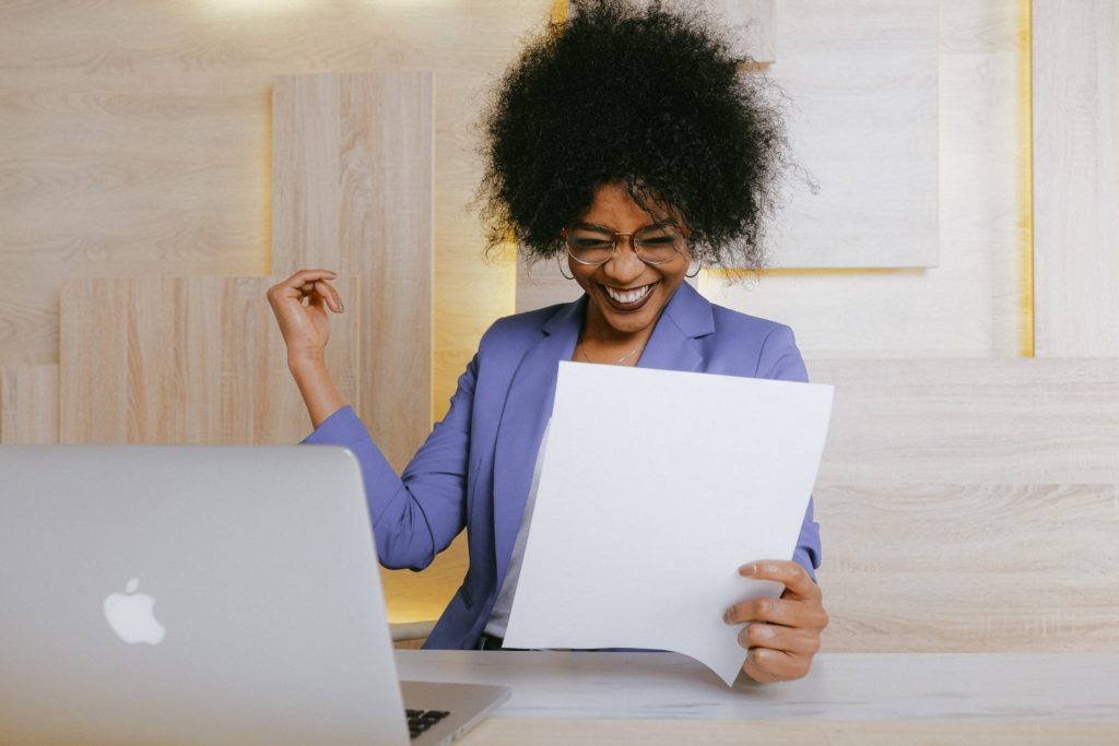 Woman sitting at a desk holding a piece of paper and excitedly smiling.
